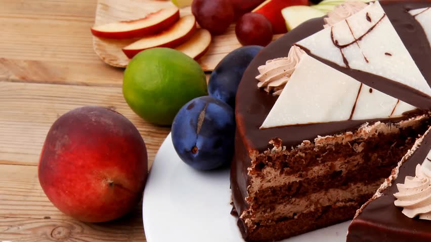 chocolate cream brownie cake layers slice topped with chocolate and cream decorated with fruits apple plum and grape on plate on wooden table with big whole cake 1920x1080 intro motion slow hidef hd