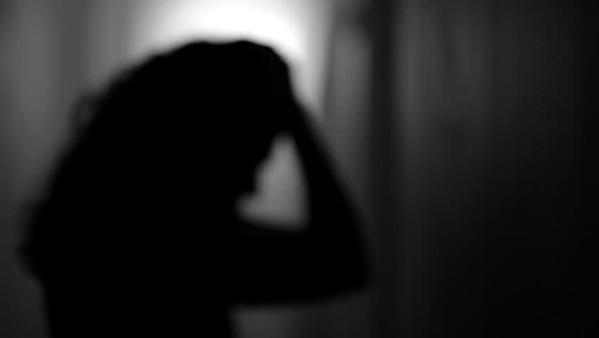 Abstract shot of a depressed woman in a dark hallway.