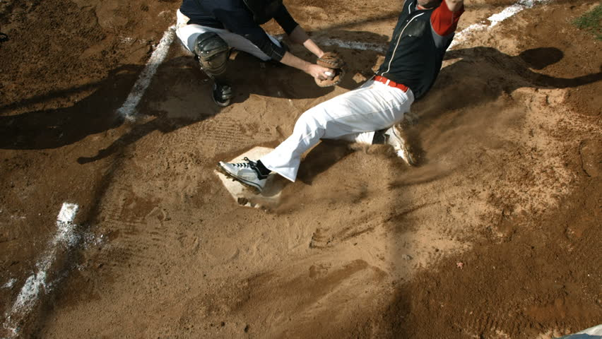 Overhead view of baseball player sliding into home plate