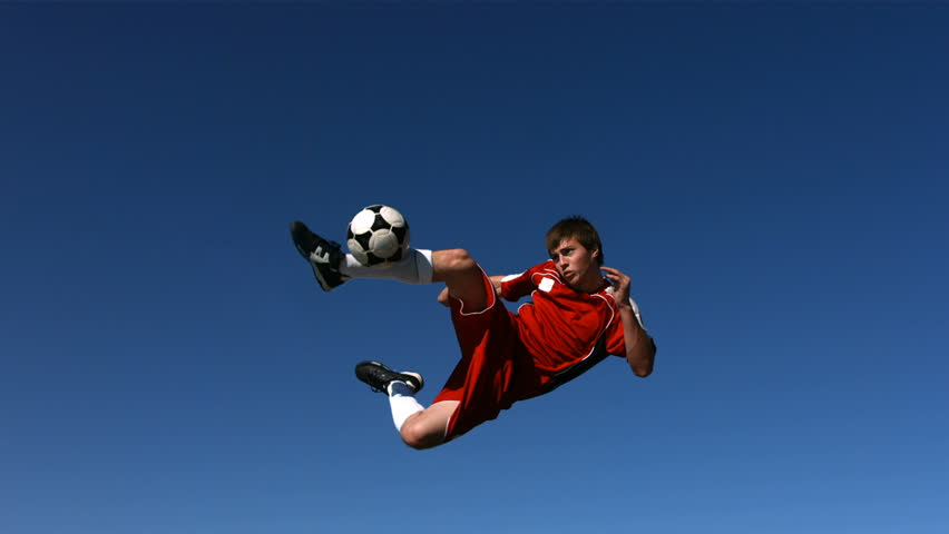 Soccer player kicking ball in mid-air, slow motion