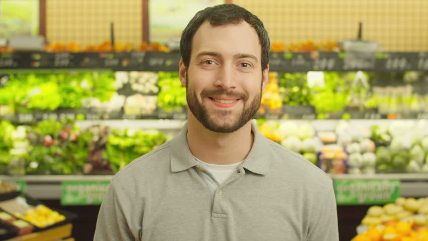 A young man walks up and smiles for the camera while in a produce section of a grocery store. Close up shot.