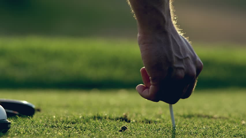A man's hand puts a tee in the ground and then sets his ball on the tee. Close up slow motion shot.