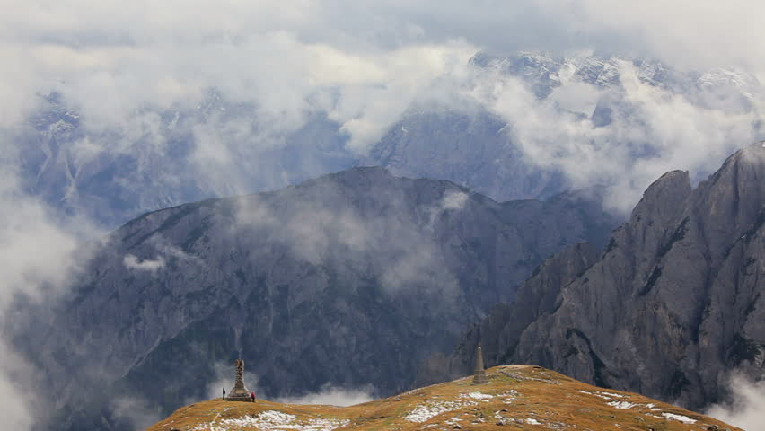 Two hikers at stone monuments at a mountain peak with a beautiful vista of the Italian Dolomites - HD stock footage clip