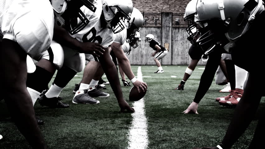 The defensive and offensive lines of two football teams meet at the line of scrimmage. High contrast, with camera flashes and time remap. - HD stock footage clip