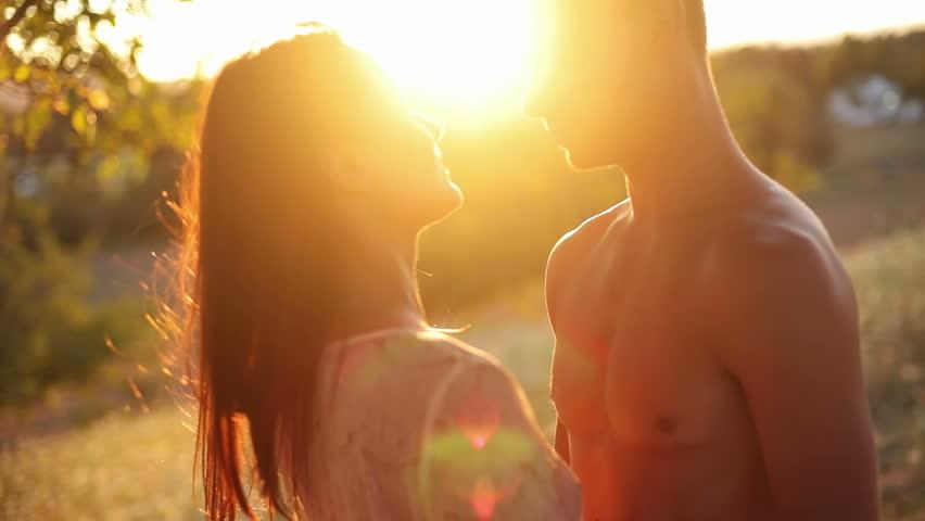 Attractive couple walk shirtless into the sunset. Medium shot.