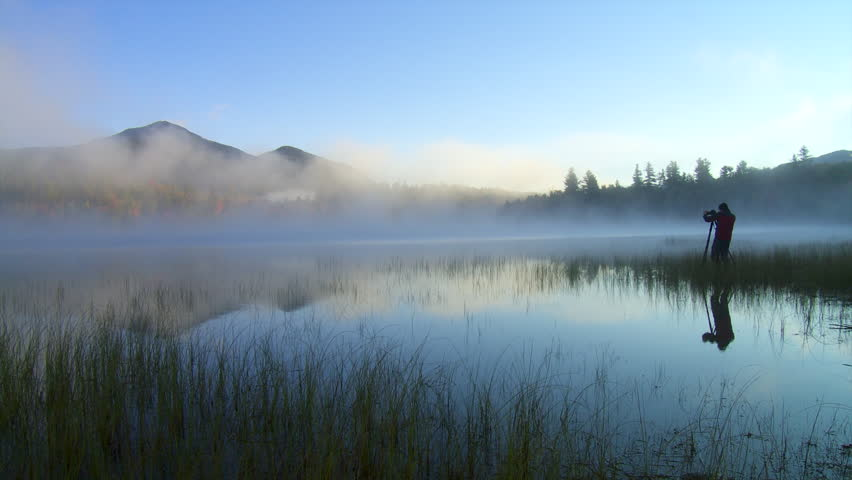 A nature photographer prepares a beautiful misty mountain scenic shot at dawn in the wilderness