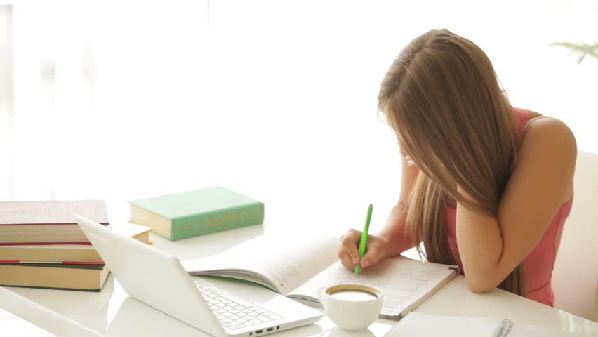 Pretty girl sitting at table studying and writing in notebook