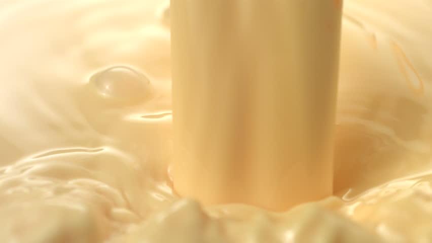 Vanilla cream pouring and splashing, slow motion