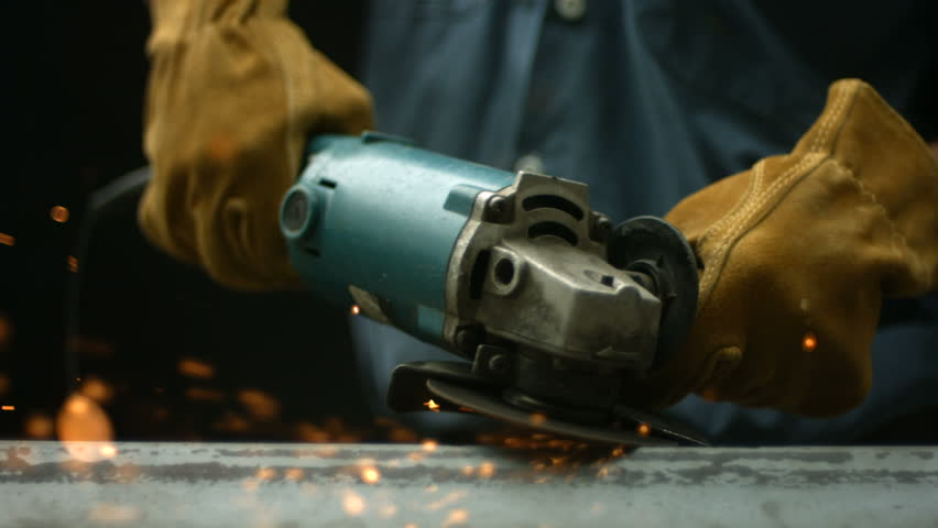 Worker using industrial grinder, slow motion