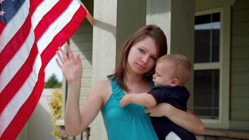 Young woman and baby say goodbye to soldier