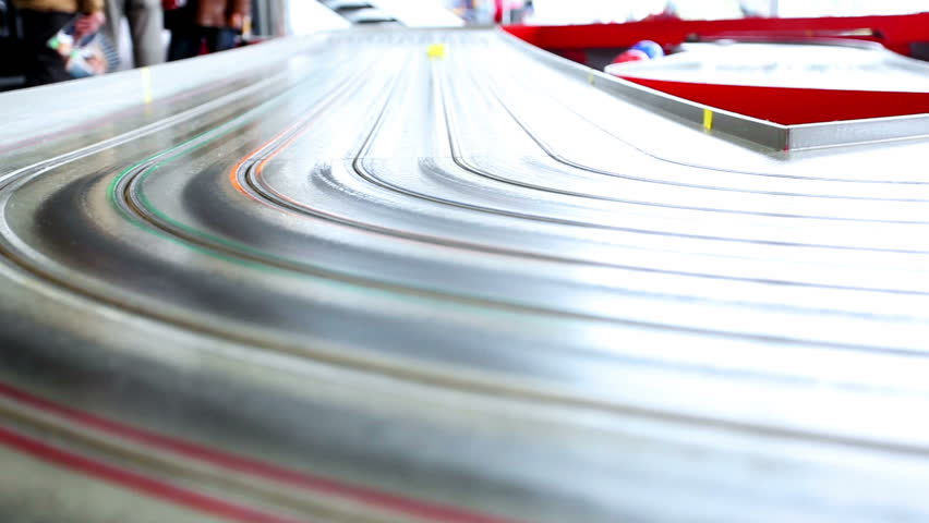 very fast small toy cars riding on huge track with extreme speed