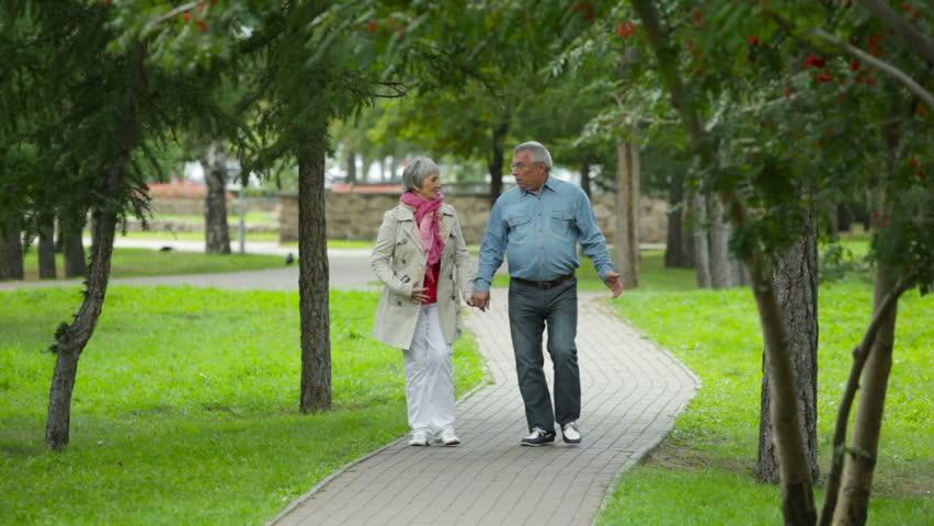 Elderly couple enjoying their weekend pastime walking outdoors - HD stock video clip
