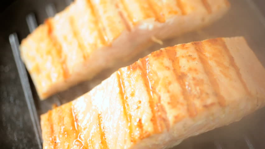 Close up view of fresh Alaskan red salmon steaks grilling on a hot griddle pan