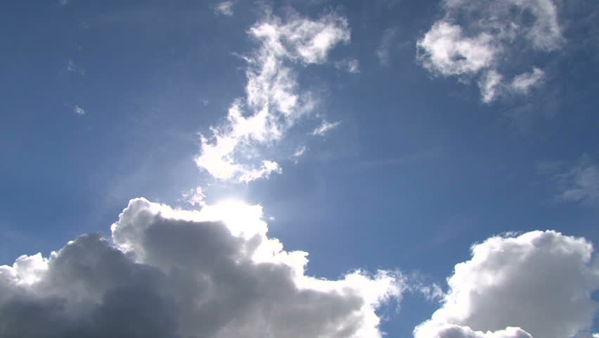 Time lapse of cloudscape with bright sun shining and revealing itself behind clouds.