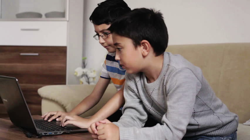 2 kids who are siblings studying working looking at a website on a notebook computer doing homework for school at home in the living room during the day
