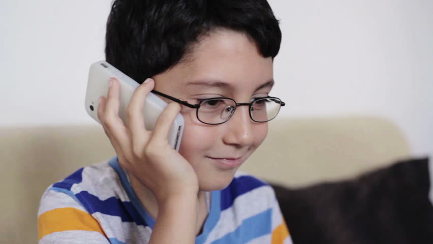 close up of young kid talking on the phone at home in the living room