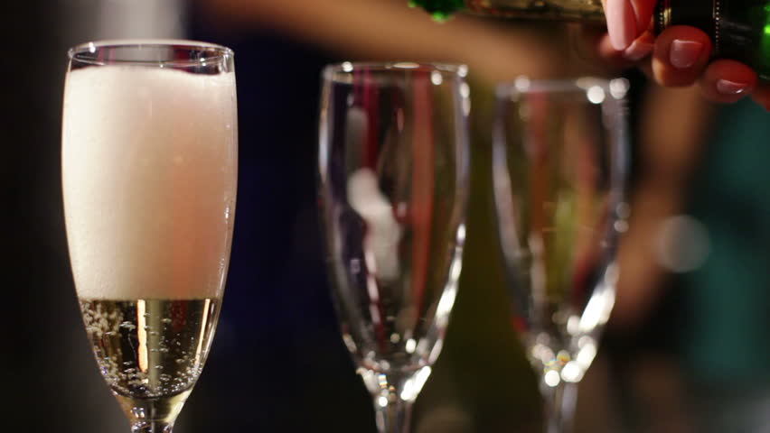 Close-up of three flutes being filled with sparkling wine