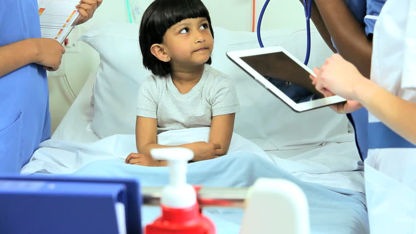 Pediatric nurses recording patient's recovery process on a wireless tablet and listening to heartbeat