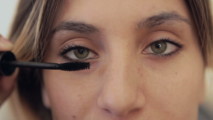 tight close up of young millenial teenage girl with brown and blonde hair putting on  makeup applying eye liner