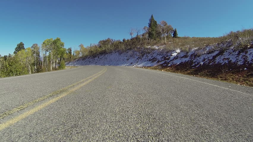 Driving mountain road POV low view. Vehicle driving high mountain road during autumn with early snow storm. Point of view with camera mounted low close to road. - HD stock footage clip