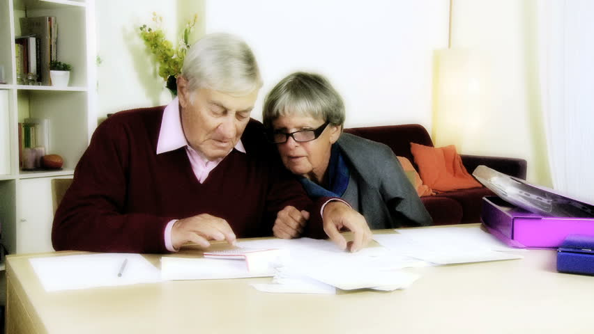Senior couple at home looking at bills and taxes  - HD stock footage clip