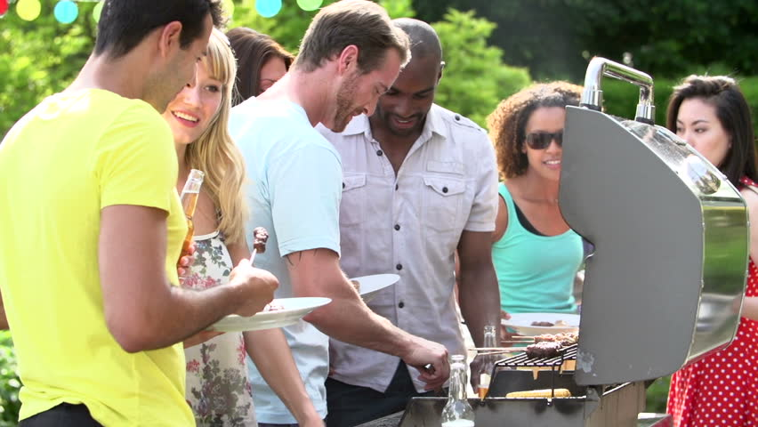 Men serving burgers, kabobs, and corn from backyard barbecue for summertime dinner party - HD stock footage clip