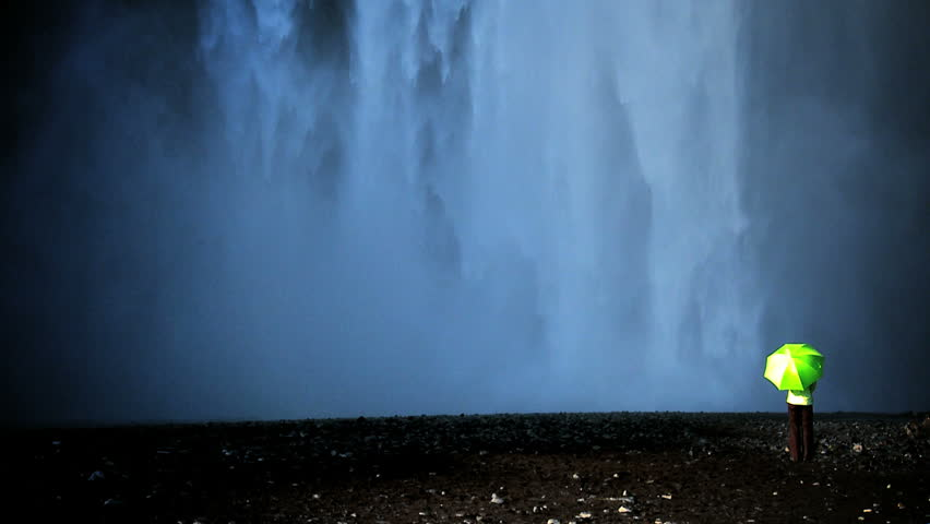 Concept shot of lone female standing on the edge of a waterfall with green umbrella to shelter from climate change 60 FPS - HD stock footage clip