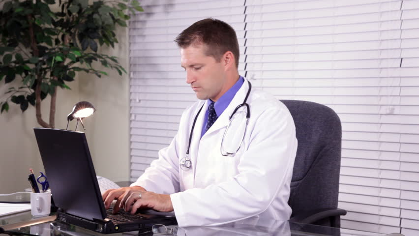 Two doctors consulting one another about test results they see on a chart and on a laptop. - HD stock footage clip