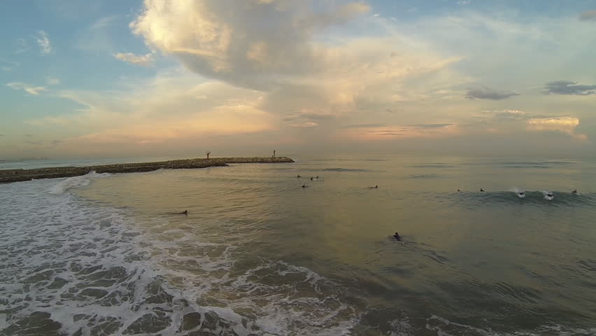 Aerial view of unidenfied people surfing at sunset