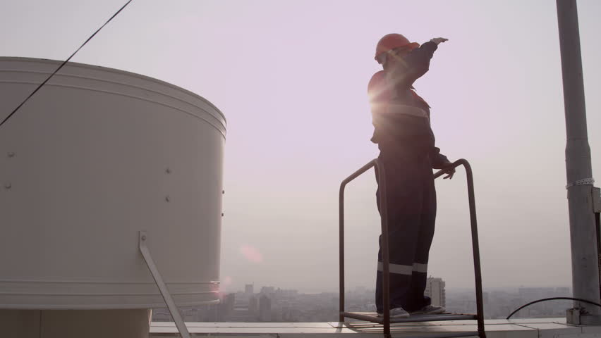 Worker in helmet climbs stairs to the roof - HD stock footage clip