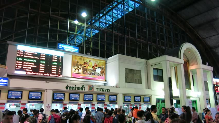 Bangkok, Thailand – October 17, 2013: Thais and tourists queue to buy tickets at Hua Lamphong Railway Station. Some walk past the ticket booths. There is a digital board showing schedule of trains.