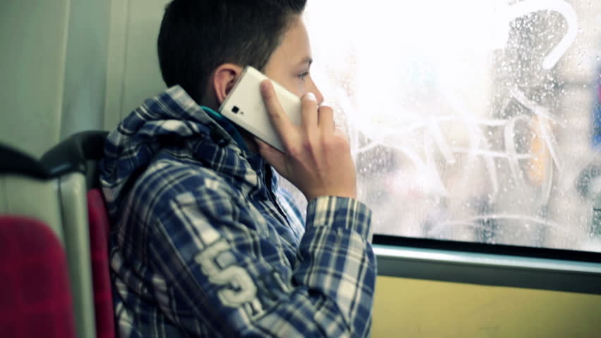 Young boy riding bus and talking on cellphone