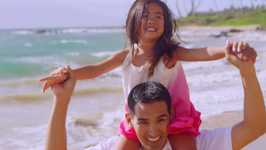A father gives his daughter a ride on his shoulders while they play at the beach - HD stock footage clip