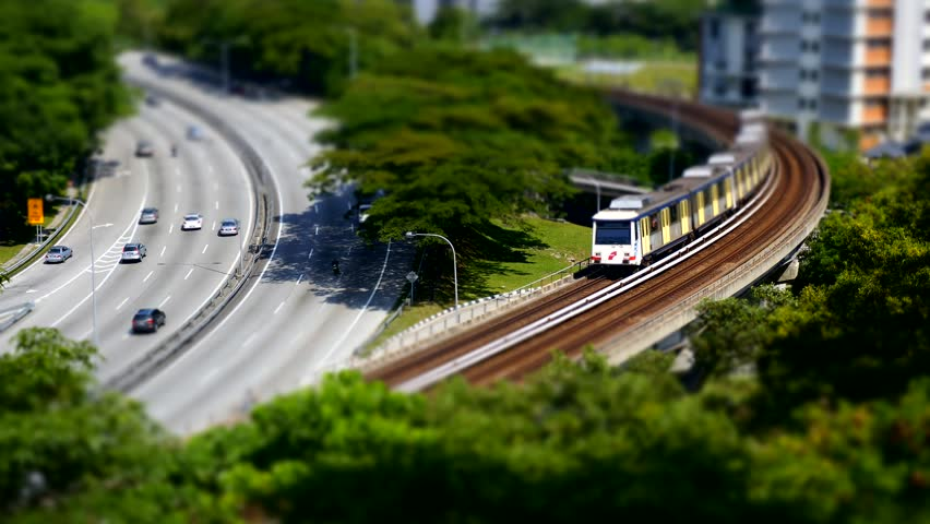 Aerial view - cars and light rail train miniature tilt shift lens effect time lapse. - HD stock footage clip