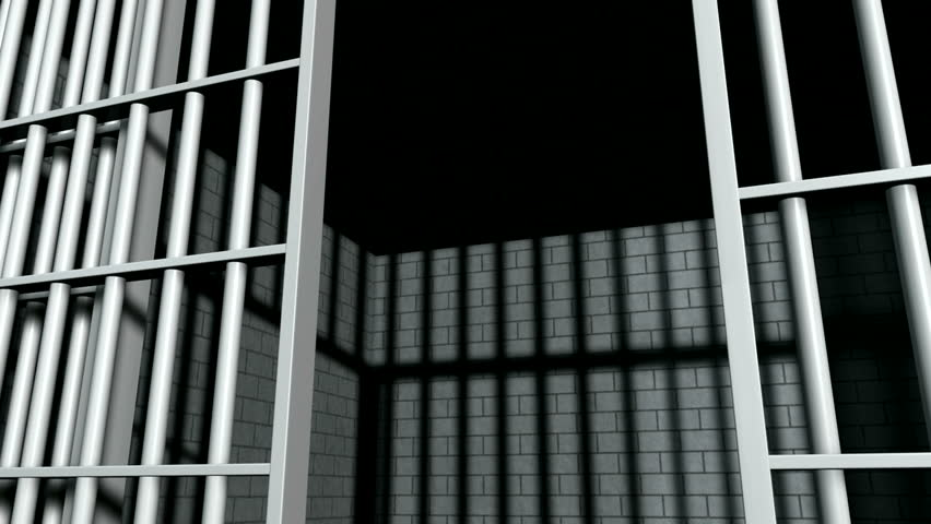 A static camera closeup of the door slamming shut a  brick jail cell with iron bars - HD stock video clip