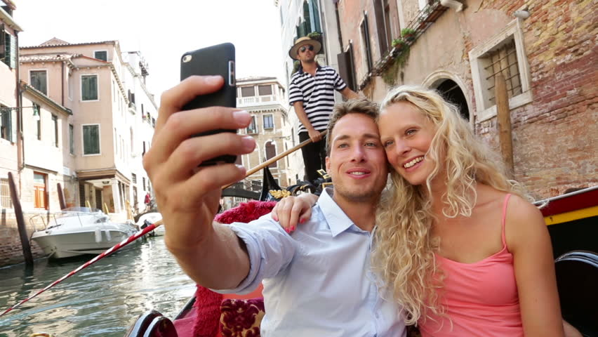 Couple in Venice on Gondole ride romance in boat happy together on travel vacation holidays. Romantic young beautiful couple taking self-portrait sailing in venetian canal in gondola. Italy.
