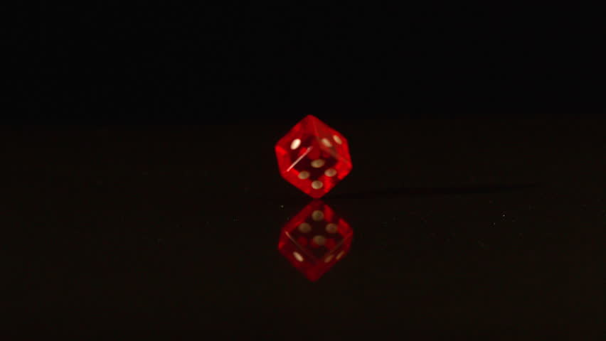 Red plastic dice revolving on black background in slow motion - HD stock footage clip