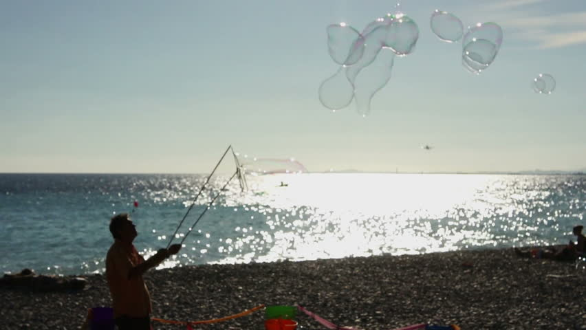 Street artist makes big soap bubbles on the beach - HD stock video clip