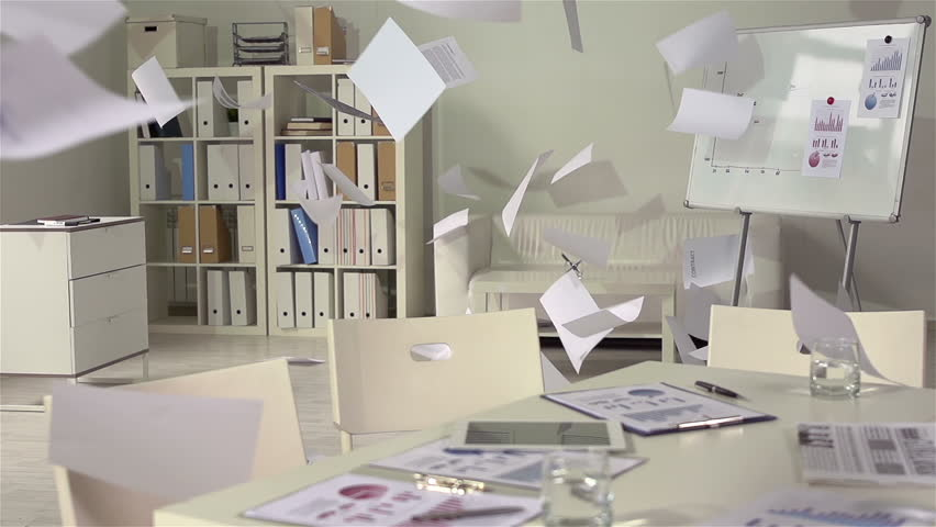 Piles of business documents falling in an empty office, slow motion