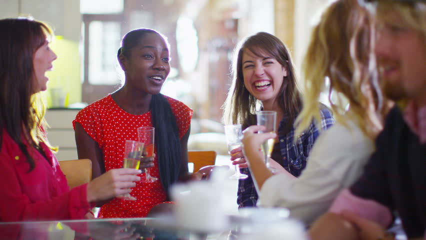 Happy group of female friends socializing and gossiping over drinks in a relaxed environment.  - HD stock video clip