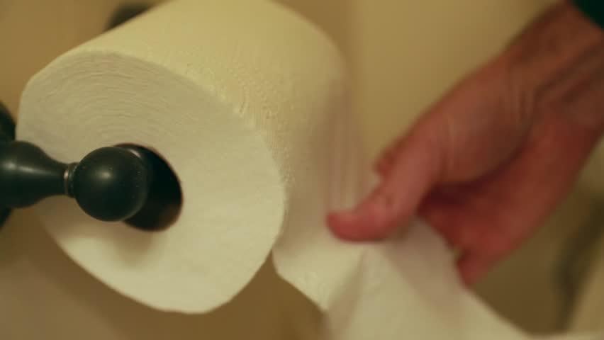 A hand grabbing toilet paper