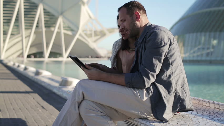 Couple with tablet computer sitting in the city