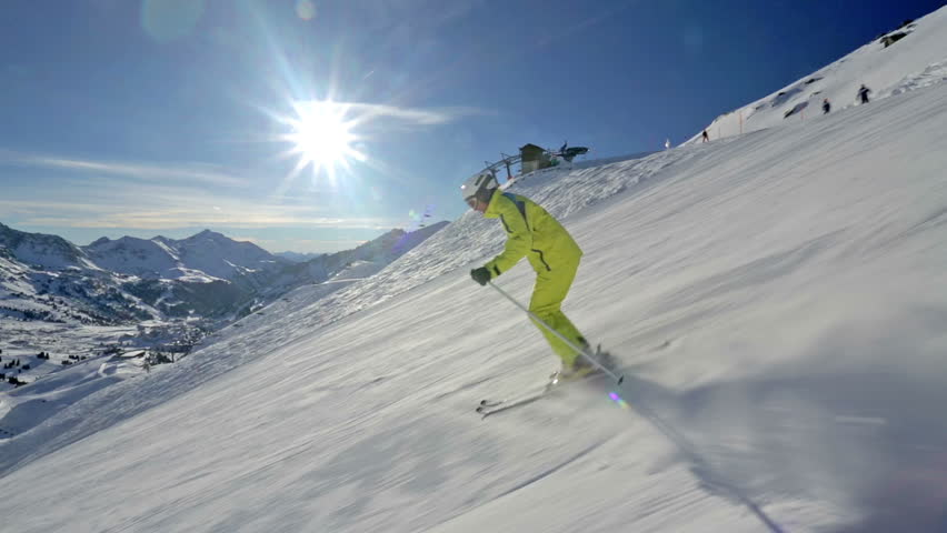 side view alpine skier skiing short swings on ski slope on sunny winter day in Austrian mountains