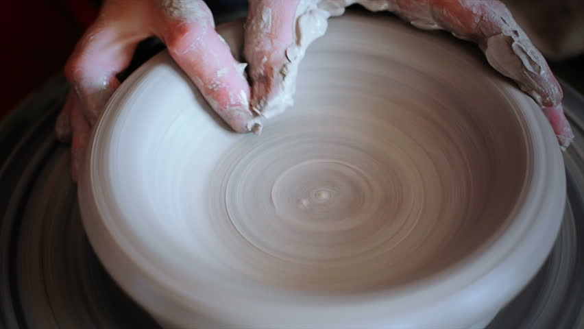 Hands working on pottery wheel, shaping a clay pot