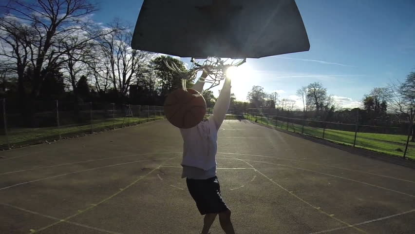 Basketball player slam dunking the ball in slow motion on an outdoor basketball court - HD stock footage clip