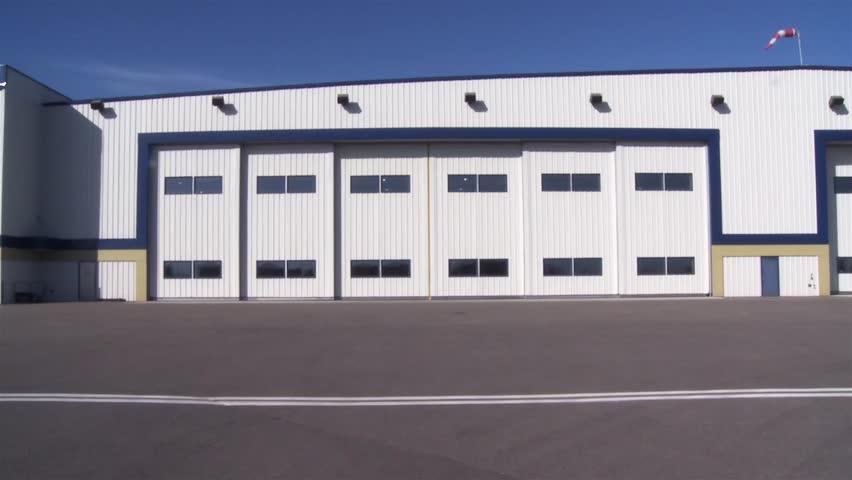 Large hangar doors open slowly.
