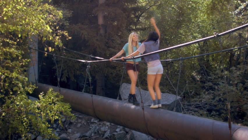 Teenage Girls Dancing, Celebrating On A Forest Walk Bridge