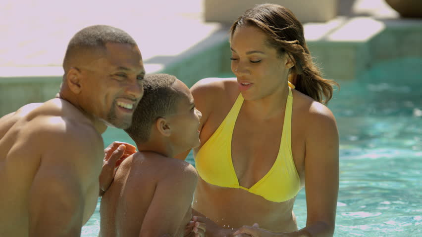 Happy young African American family enjoying healthy swimming lifestyle outdoor pool luxury vacation accommodation shot on RED EPIC, 4K, UHD, Ultra HD resolution - 4K stock video clip
