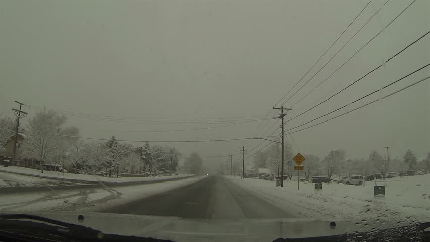 Driving winter snow storm urban city street POV HD. Winter snow storm hit West and Midwest USA with extreme cold weather and snow. Dangerous driving conditions on snow packed and icy roads. - HD stock video clip