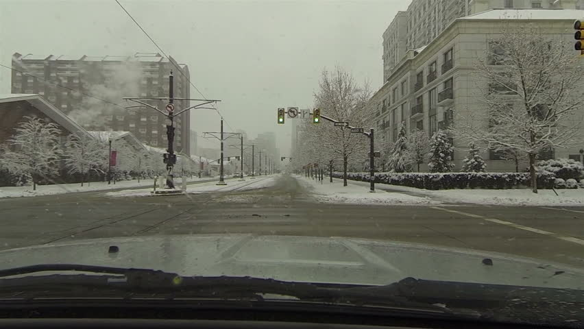 Urban street winter snow storm blizzard drive POV HD. Winter snow storm hit West and Midwest USA with extreme cold weather and snow. Dangerous driving conditions on snow packed and icy roads. - HD stock video clip